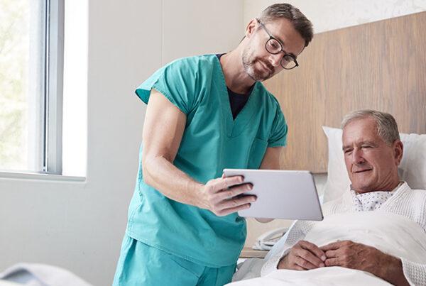 enfermeiro mostrando um tablet conectado ao wifi inteligente para o paciente deitado